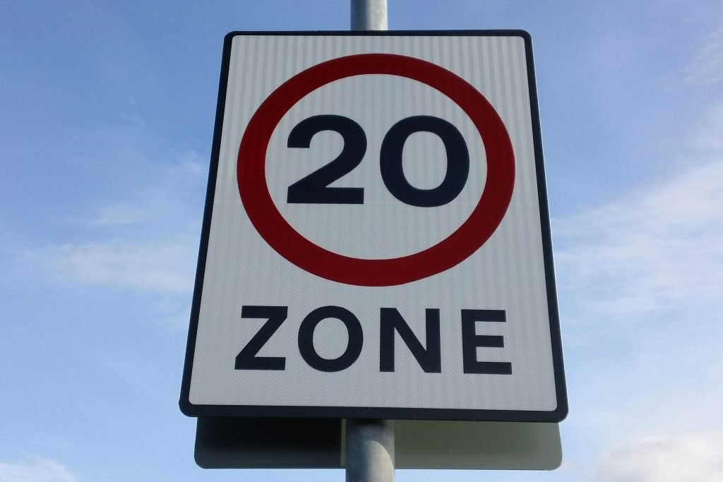 White 20mph sign with blue sky behind